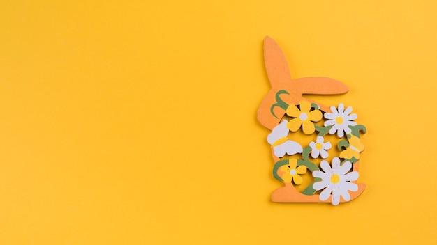 Coniglio in legno con fiori sul tavolo giallo Foto Gratuite