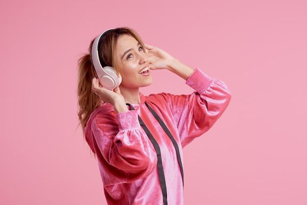 Connessione senza fili. ritratto di giovane donna in posa isolato su sfondo rosa ascolto musica divertente con le cuffie. Foto Premium
