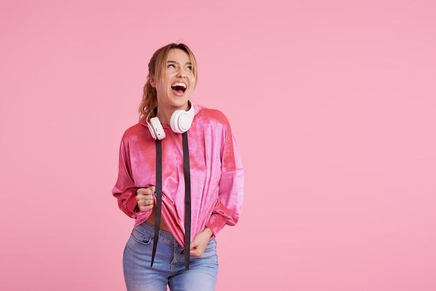 Connessione senza fili. ritratto di posa della giovane donna isolato sopra musica d'ascolto rosa di divertimento con le cuffie. Foto Premium