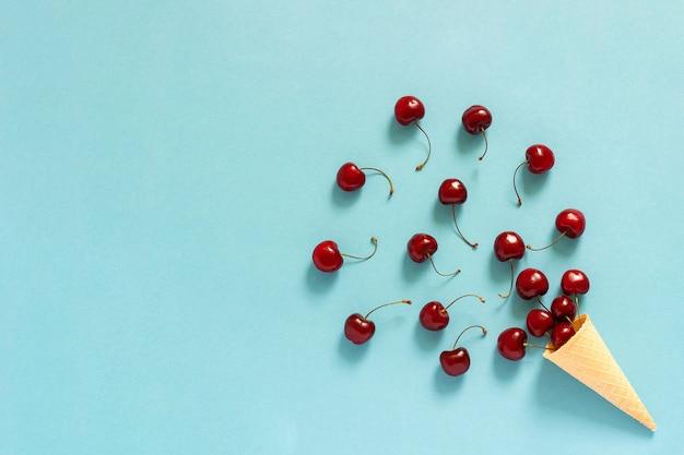 Cono gelato cialda e ciliegie rosse sparse Foto Premium
