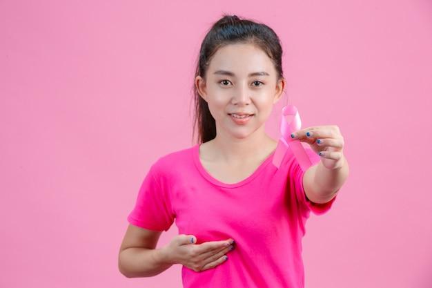 Consapevolezza del cancro al seno, una donna che indossa una camicia rosa con in mano un nastro rosa con la mano sinistra mostra il giorno simboleggiante contro il cancro al seno Foto Gratuite