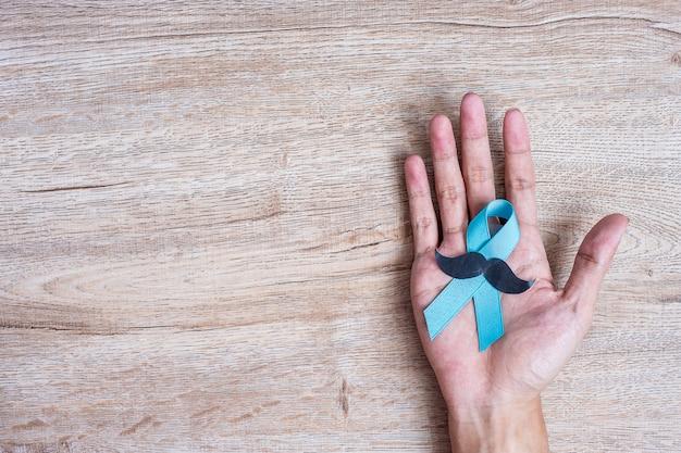 Consapevolezza del cancro alla prostata, uomo che tiene il nastro azzurro con i baffi Foto Premium