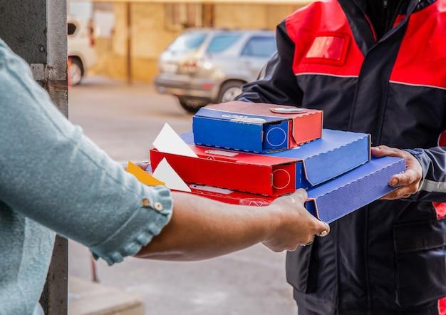 Consegna pizza. un corriere che consegna scatole per pizza a una persona. Foto Gratuite