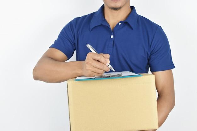 Consegna . scatola di consegna consegna giovane e scrivere qualcosa negli appunti. Foto Premium