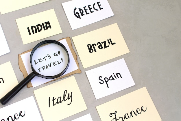 Consente di andare parole di testo di viaggio, selezione del paese, bussola lente di ingrandimento mappa, sfondo grigio Foto Premium
