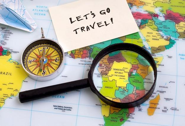 Consente di andare parole di testo di viaggio, selezione del paese, bussola lente di ingrandimento mappa, sfondo Foto Premium