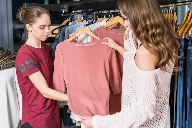 Consulente femminile che aiuta donna che compera al negozio di abbigliamento Foto Gratuite