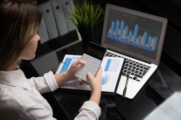 Consulente in materia di investimenti della donna di affari che analizza il bilancio di bilancio finanziario annuale della società Foto Premium