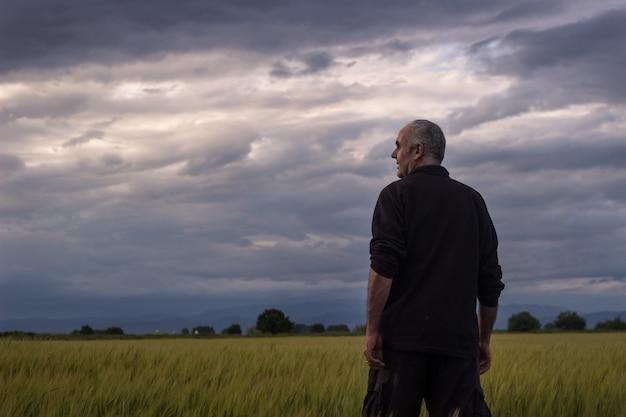 Contadino in un giorno di tempesta a guardare il raccolto Foto Premium