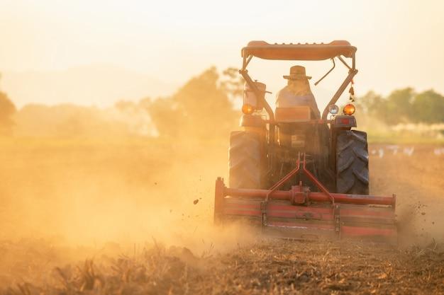 Contadino sul grande trattore nella terra per preparare il terreno Foto Premium