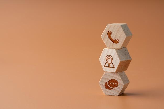 Contattaci icona su puzzle di legno con la mano Foto Premium