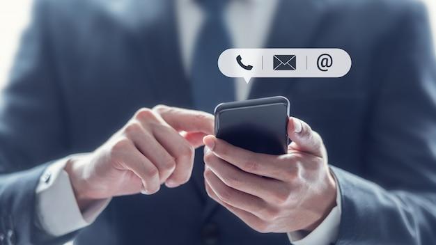 Contattaci, mano dell'uomo d'affari che tiene smartphone mobile con l'icona (posta, telefono, e-mail). Foto Premium