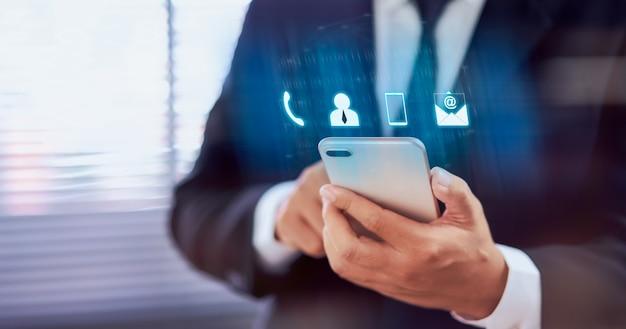 Contattici concetto, smartphone della tenuta della mano dell'uomo d'affari con la call center di servizio di assistenza al cliente dell'icona. Foto Premium