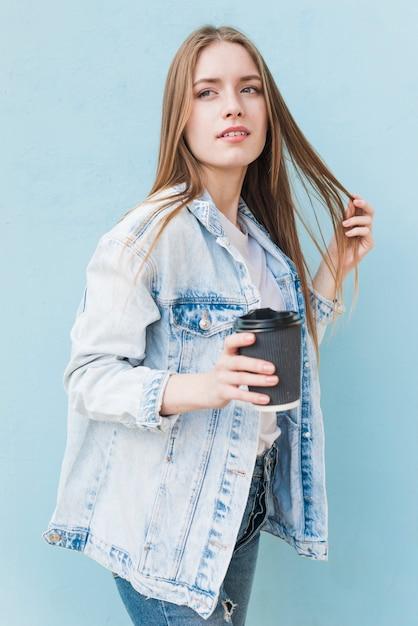 Contemplando la giovane donna che tiene il caffè a gettare che sta davanti alla parete blu Foto Gratuite