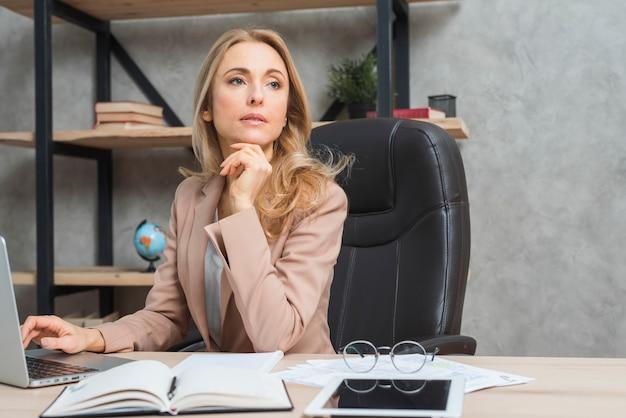 Contemplato giovane imprenditrice con laptop; diario; tavoletta digitale sullo scrittorio di legno Foto Gratuite