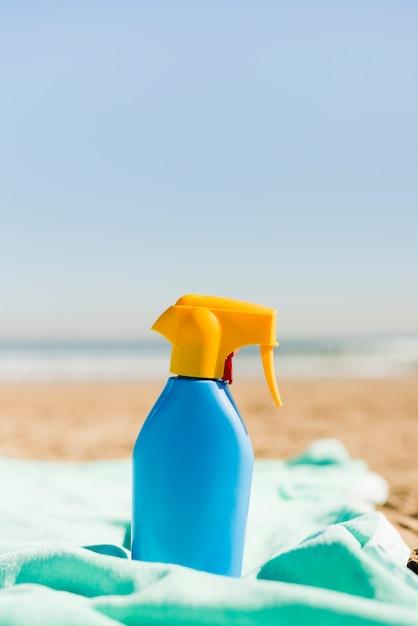 Contenitore blu chiuso dei cosmetici della protezione solare sulla coperta del turchese alla spiaggia Foto Gratuite