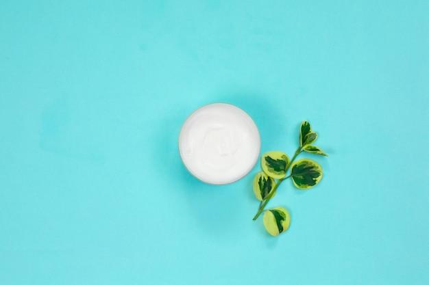 Contenitore crema cosmetica con foglie verdi Foto Premium