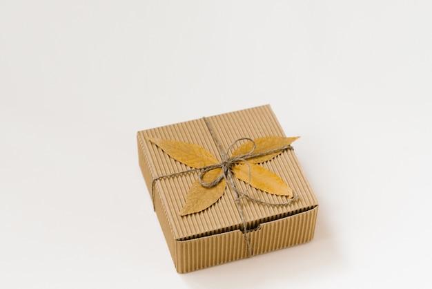 Contenitore di regalo artigianale, legato con spago con fiocco e foglie cadute in autunno su uno sfondo beige Foto Premium