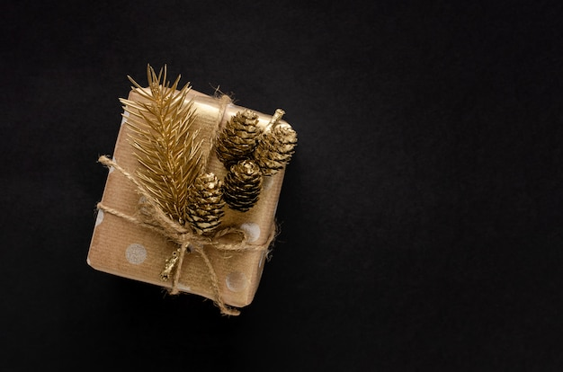 Contenitore di regalo avvolto in carta del mestiere con abete e cono dorati sul nero Foto Premium