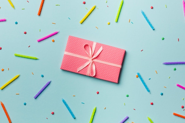 Contenitore di regalo avvolto intorno alle candele variopinte e spruzza sul contesto blu Foto Gratuite