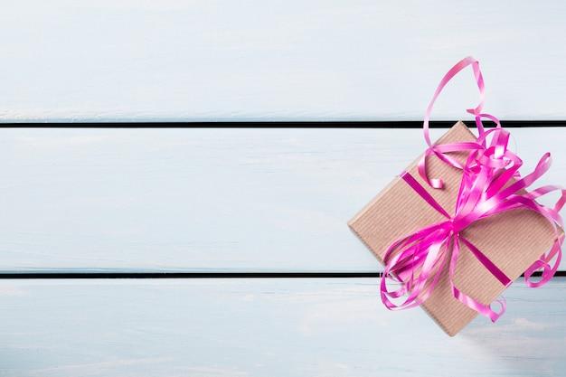 Contenitore di regalo con il nastro rosa piacevole su fondo di legno blu Foto Premium