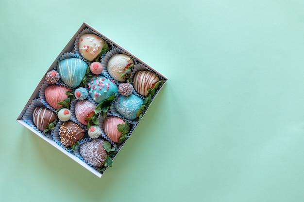 Contenitore di regalo con la fragola fatta a mano in cioccolato su fondo verde con spazio libero per testo Foto Premium