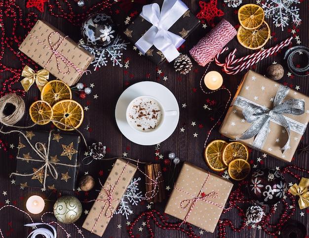 Contenitore di regalo della bevanda della tazza di caffè di festa di natale sulla tavola festiva decorata con la candela del bastoncino di zucchero delle pigne Foto Gratuite