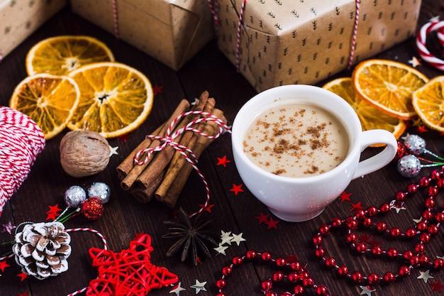 Contenitore di regalo della bevanda della tazza di caffè di festa di natale sulla tavola festiva decorata Foto Gratuite