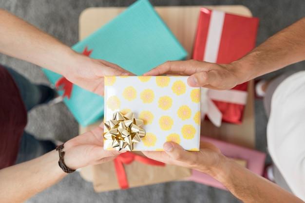 Contenitore di regalo della holding della mano dell'amico maschio con l'arco del nastro dorato Foto Gratuite