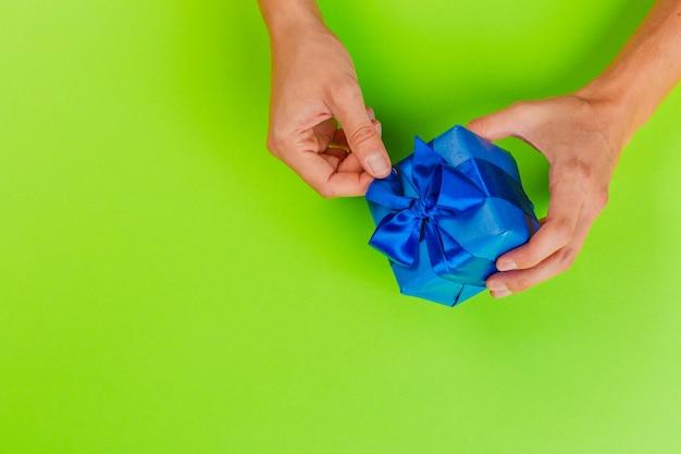 Contenitore di regalo della tenuta della donna sul fondo di colore Foto Premium