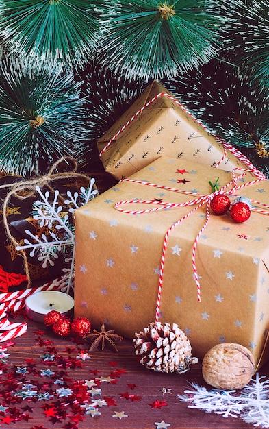Contenitore di regalo di festa di natale sulla tavola festiva decorata con le noci del bastoncino di zucchero dei rami dell'abete delle pigne Foto Gratuite