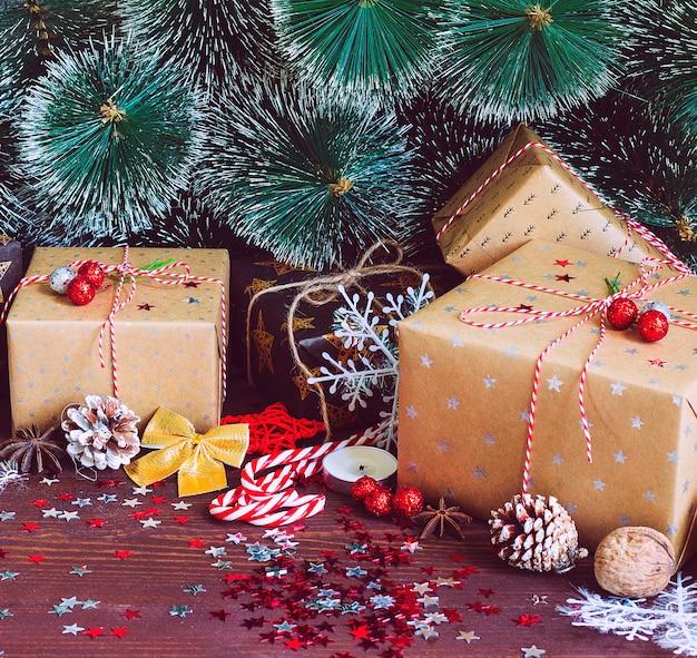 Contenitore di regalo di festa di natale sulla tavola festiva decorata con rami di abete di pigne Foto Gratuite
