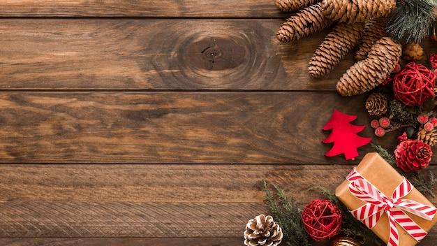 Contenitore di regalo di natale con i coni sul tavolo Foto Gratuite