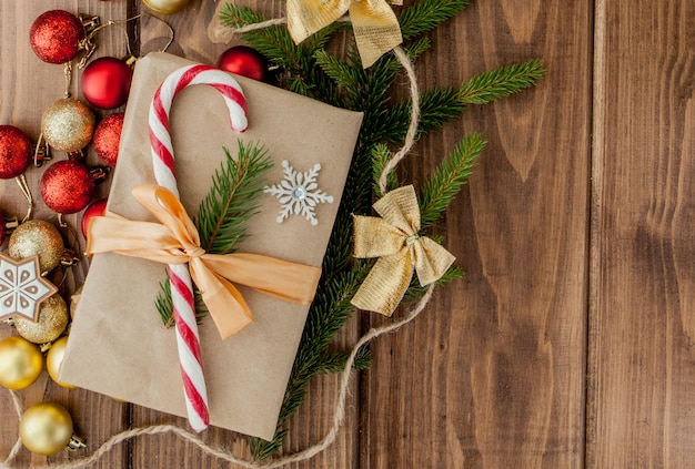Contenitore di regalo di natale, decorazione e ramo di albero di abete sulla tavola di legno. vista dall'alto con copyspace Foto Premium