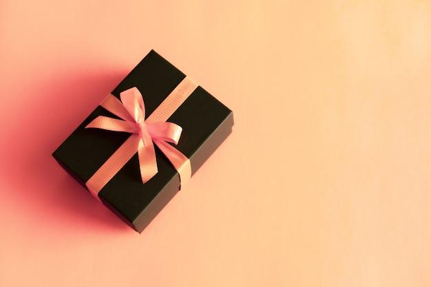 Contenitore di regalo nero con fiocco arancione su sfondo rosa corallo pastello. stile minimal festivo piatto laico. Foto Premium