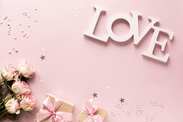 Contenitore di regalo o contenitore e fiori di regalo sulla vista rosa del piano d'appoggio. Foto Premium