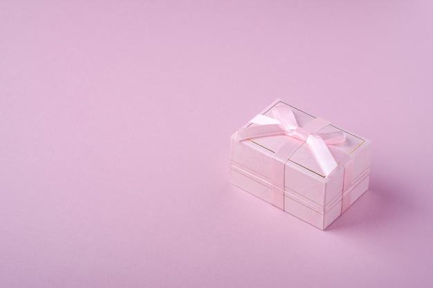 Contenitore di regalo rosa con il nastro su fondo rosa molle, vista di angolo, spazio della copia Foto Premium