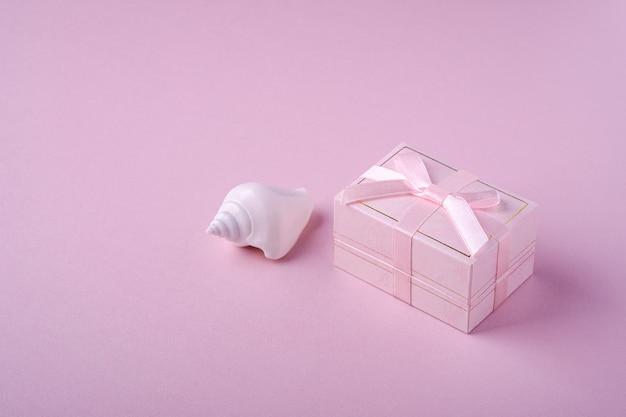 Contenitore di regalo rosa con il nastro vicino alla conchiglia bianca su fondo rosa molle, vista di angolo, spazio della copia Foto Premium
