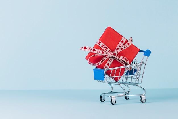Contenitore di regalo rosso avvolto in carrello su fondo blu Foto Gratuite