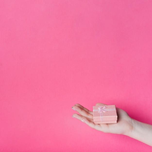 Contenitore di regalo sulla mano della palma della femmina contro fondo bianco Foto Gratuite