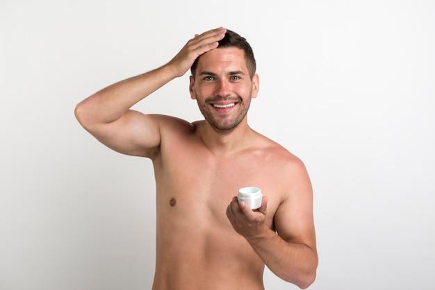 Contenitore sorridente della crema per capelli della tenuta del giovane ed esaminare macchina fotografica Foto Gratuite
