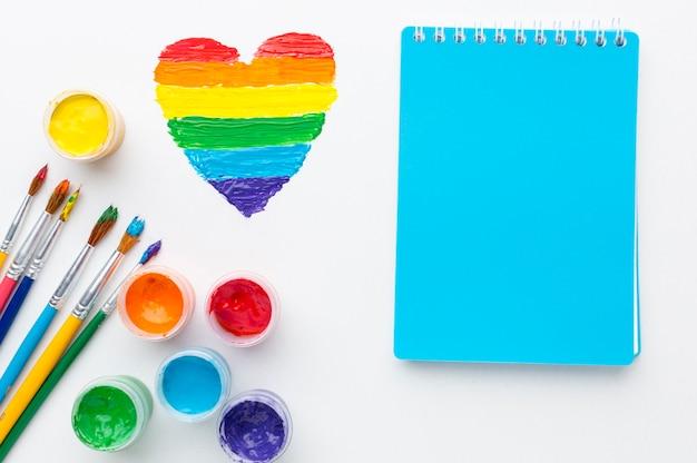 Contenitori arcobaleno di vernice per orgoglio amore e blocco note Foto Gratuite