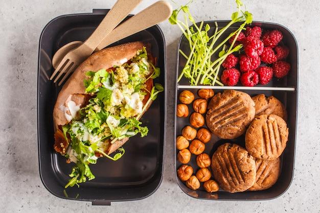 Contenitori di preparazione pasti sani con quinoa patate dolci farcite, biscotti e frutti di bosco, colpo di testa. Foto Premium