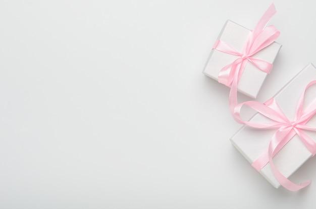 Contenitori di regalo con il nastro rosa su fondo bianco. Foto Premium