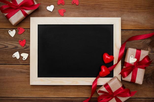 Contenitori di regalo con il nastro rosso e lavagna vuota sulla tavola di legno. vista dall'alto. Foto Premium