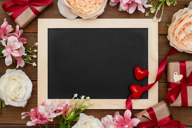 Contenitori di regalo con il nastro rosso, la disposizione dei fiori e la lavagna vuota sulla tavola di legno. Foto Premium