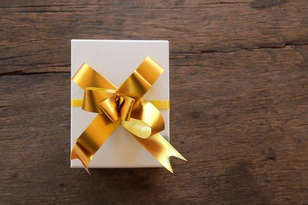 Contenitori di regalo con il nastro su fondo di legno marrone, vista superiore con copia-spazio Foto Premium