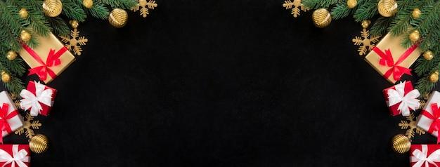 Contenitori di regalo di natale ed ornamenti di decorazione dorati lucidi sulla priorità bassa della lavagna Foto Premium