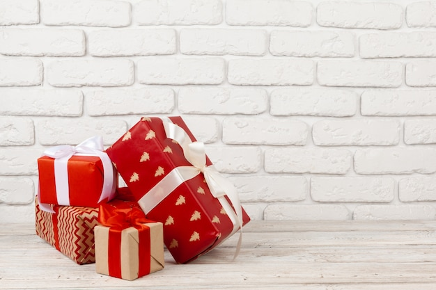 Contenitori di regalo variopinti contro il fondo bianco del muro di mattoni Foto Premium