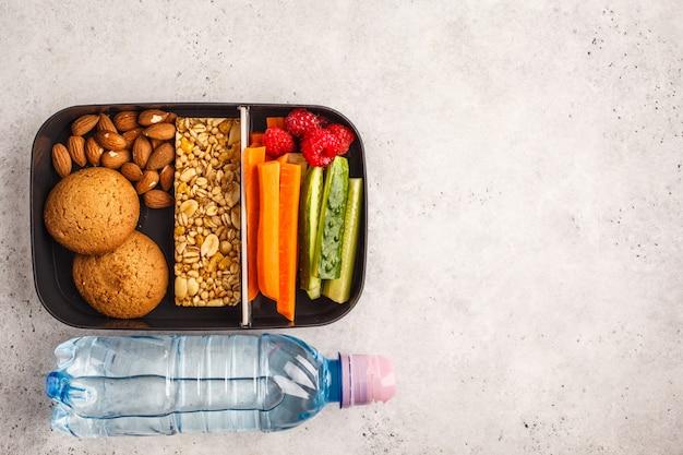Contenitori per preparare pasti sani con barretta ai cereali, frutta, verdura e snack. alimento da asporto su fondo bianco, vista superiore. Foto Premium